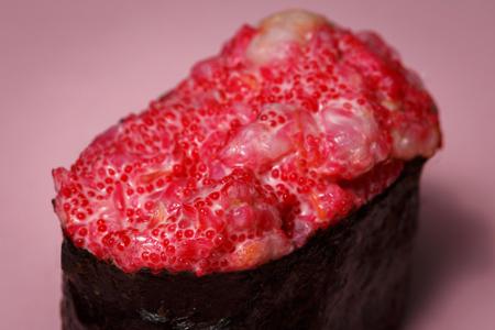 Japanese food Ebiko Gunganmaki. Shrimp roe gunship roll isolated on pink background.