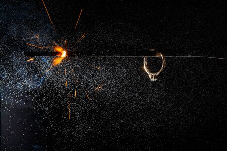 Wedding engagement ring on burning bengal light with many sparks and water spray on dark background. Marriage proposal for Christmas. Stock Photo