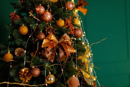 Beautiful New Year Tree decorated with colorful packed gifts and balls in studio against green background with empty placespace for Christmas text postcard concept.