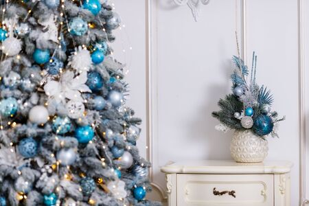 Beautiful New Year Tree decorated with colorful packed gifts and balls in studio against white background with empty placespace for Christmas text postcard concept.