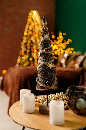 Toy decorative Christmas tree on a table with candles 스톡 콘텐츠