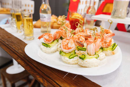 Snack on white bread with fried shrimp and cucumber on a skewer 免版税图像 - 150666563