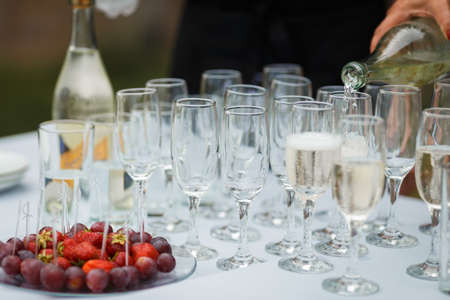 Waiter pours champagne in glasses on the street