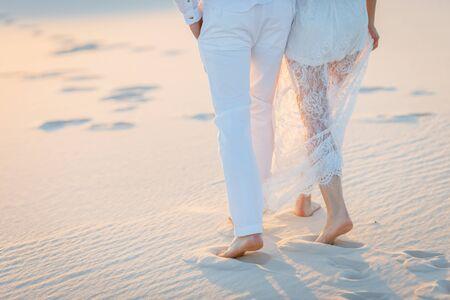 Lovers walk barefoot on the sand in the white desert. Love in the desert newlyweds.