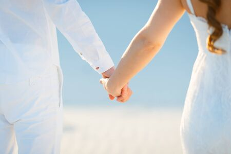 Happy couple walking holding hands in the white desert.