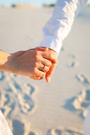 Hands of newlyweds. Bride and groom holding their hands. Young happy man makes an offer of hand and heart to his beloved girl.