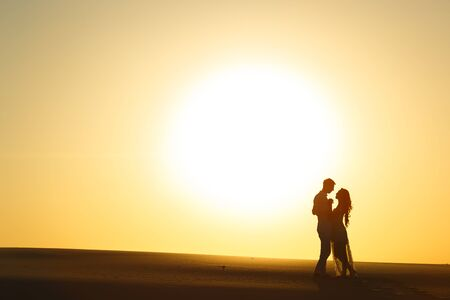 Newlyweds walk barefoot on the sand in the white desert at sunset.