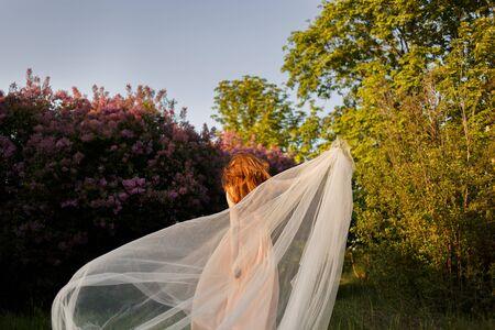Beautiful fine art bride with a veil in a lilac garden 免版税图像