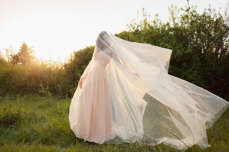 Fine Art Portrait of a beautiful bride with a veil in a summer garden