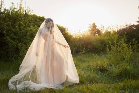 Portrait of a beautiful young brunette bride woman in a dress and with a long veil Curling in the wind on the nature garden in the summer. Fine art, wedding.