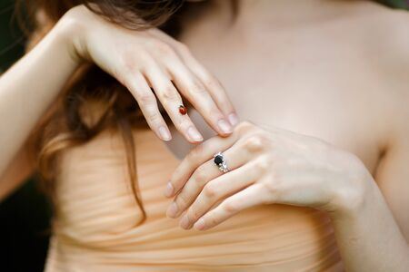 Close-up portrait of beautiful female model with ladybug on her finger outdoor. 免版税图像