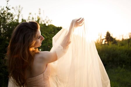 Bride's hands under the long veil with white gold engagement ring