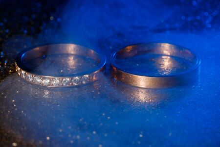 A pair of gold wedding rings with blue neon bokeh background with smoke.