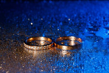 Wedding rings with water drops on a dark blue neon backlight background.