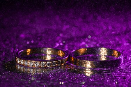 Wedding rings with water drops on a dark violet neon backlight background.