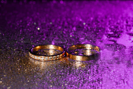 Wedding rings with water drops on a dark violet neon backlight 免版税图像 - 150666808