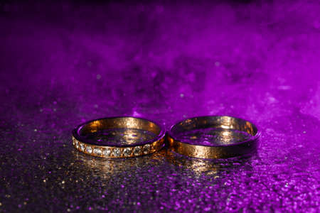 A pair of gold wedding rings with blue neon bokeh  with smoke. 免版税图像 - 150666807