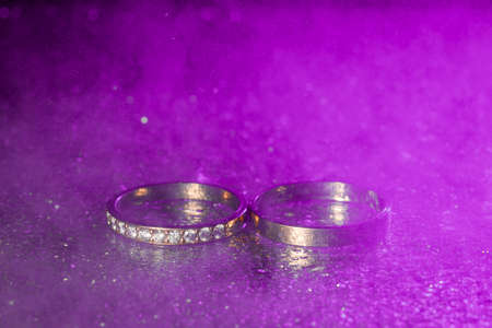 A pair of gold wedding rings with blue neon bokeh  with smoke.
