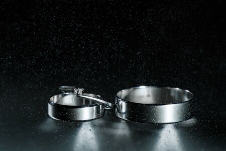 Beautiful wedding silver rings on dark wet glass with water drops. 免版税图像 - 149304451
