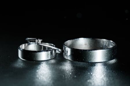 Beautiful wedding silver rings on dark wet glass with water drops.