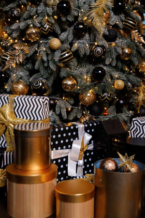 Many gift boxes and christmas decorations under a beautiful decorated christmas tree.