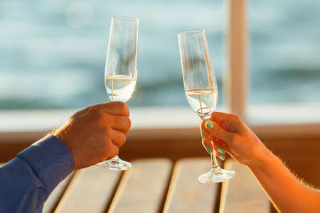 Happy couple drinks champagne on a yacht.