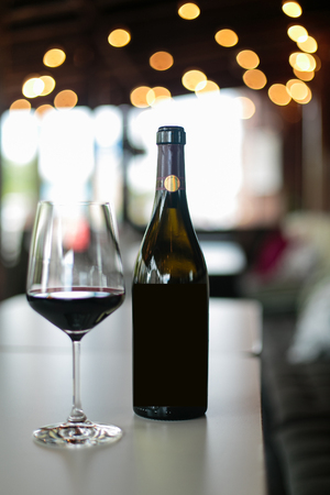 red wine bottle and wine glass on table Stock Photo