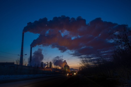 electric generating plant: Smoke from  big tubes of heat station at night