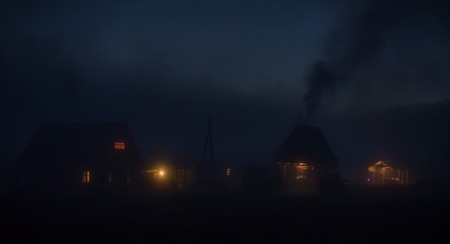earlier: Night old forest tourist village houses in earlier morning mist