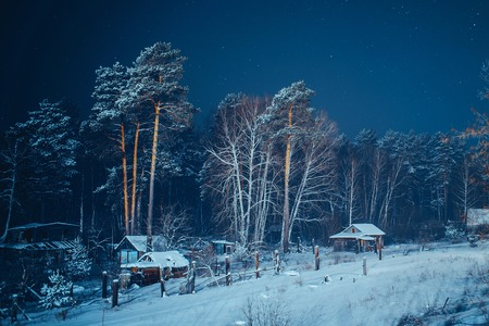cottage: Small houses in a snow covered winter forest in small village at night Stock Photo