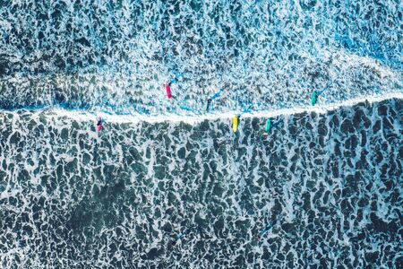 Ocean waves with surfers aerial top to down photo