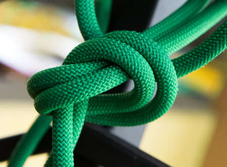 Close up green rope with knot on selective focus background