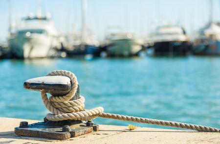 Afmeren touw en meerpaal op zeewater en jachten achtergrond Stockfoto