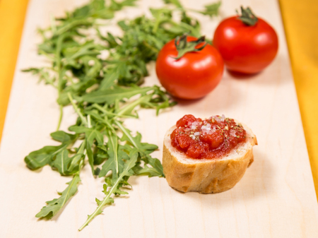 Slice of bread with tomato paste, spices and salt with fresh tomatos and rocket salad on a wooden kitchen board