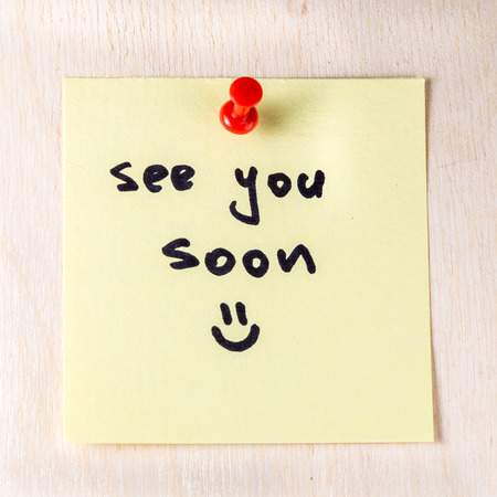 See you soon note on paper post it pinned to a wooden board 스톡 콘텐츠