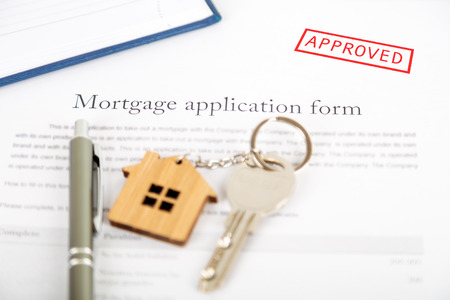 Approved mortgage loan agreement application with a house shaped keyring Stok Fotoğraf - 106732004