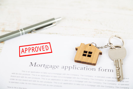 Approved mortgage loan agreement application with a house shaped keyring