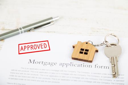 Demande d'accord de prêt hypothécaire approuvée avec un porte-clés en forme de maison