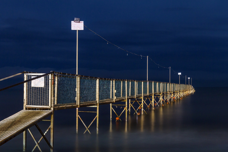 Night view of old wooden pier going into the sea. Adventure and challange concept