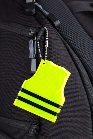 Yellow pedestrain safety reflector on a black backpack, closeup view. Concept of safety