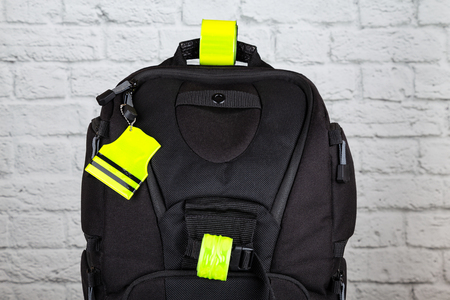 Black backpack with pedestrain safety reflectors. Concept on safety on the road