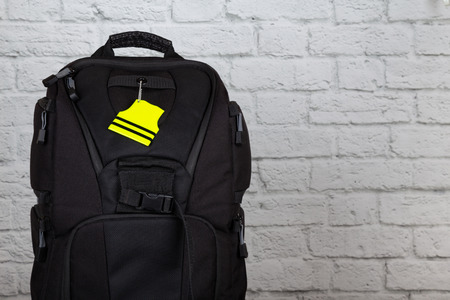 Black backpack with pedestrain safety reflectors with copy space. Safety on the road