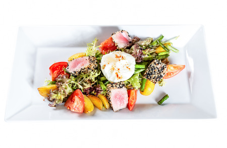 Plate of nicoise salad with roasted tuna and  poached egg isolated on white
