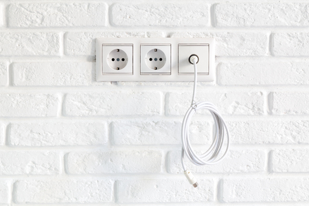 Row of power and tv sockets and tv cable on brick wall. Concept of TV set stolen or sold for debts