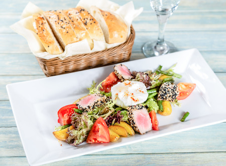 Plate of nicoise salad with roasted tuna and poached egg on wooden table