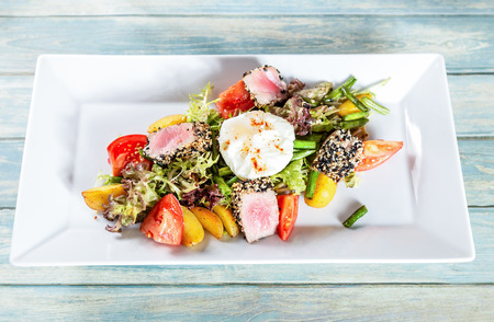 Plate of nicoise salad with roasted tuna and  poached egg
