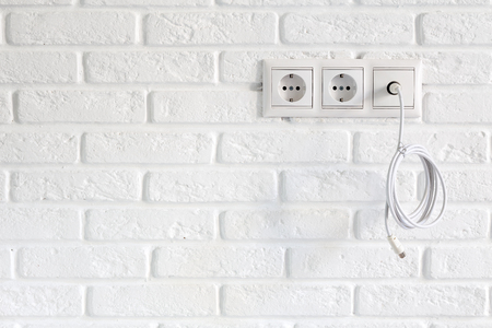 Row of power and tv sockets and tv cable on brick wall with copy space Reklamní fotografie