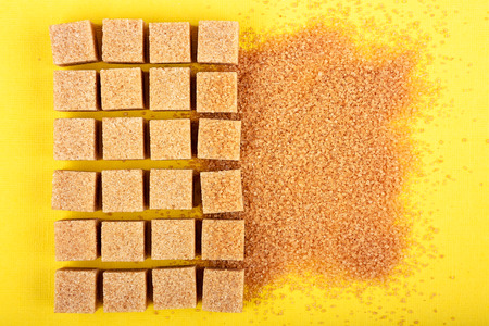 Brown sugar. Mix of cubes and sand on yellow background Archivio Fotografico