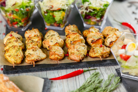 Chicken kebabs on  a wooden table