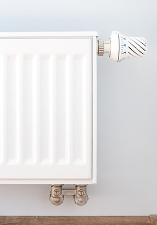 Interior detail. White metal radiator on a white wall Stock Photo